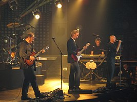 Genesis performing live on their 2007 US tour in Pittsburgh. (Left to right: Daryl Stuermer (guitar), Mike Rutherford (guitar and bass guitar), Tony Banks (keyboards), Phil Collins (lead vocals and drums).)
