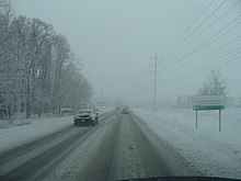 A one-way toad line with trees on the left and power lines on the right during a snowstorm