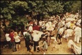 AUDIENCE AT AN AUCTION OF HOUSEHOLD GOODS IN A RESIDENTIAL AREA. THEY USUALLY ARE HELD IN THE SUMMER MONTHS TO SELL... - NARA - 558294.tif