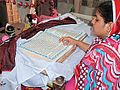 A woman reciting the Gita at the Sadh Belo temple on the special occasion of the 150th death anniversary of Baba Bhankandi Maharaj.jpg