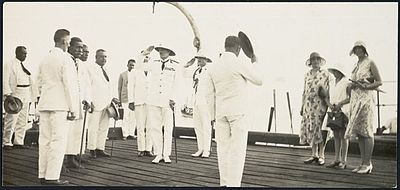 Several men dressed in white tropical uniforms on the deck of a ship, two men wearing pith helmets are saluting, and a group of women wearing dresses and hats are standing to one side