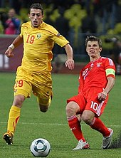 Two white footballers during an international football match between Macedonia and Russia. The footballer in yellow is dribbling past the footballer in red.