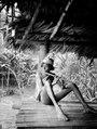 Alipio, en chocógosse, blåser flöjt. Han bär en huvudprydnad av palmblad. Rio Sambú, Darién, Panamá - SMVK - 004080.tif