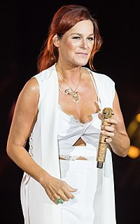 A red-haired woman performing on stage. She is wearing a white outfit and holding a golden microphone.