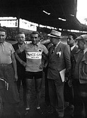 Photographie en noir et blanc montrant un coureur debout à côté de son vélo, entouré par des officiels.