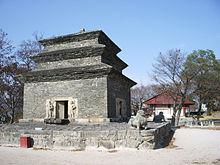 Un'enorme pagoda a tre piani si staglia contro il cielo azzurro.  La pagoda è realizzata con mattoni di pietra grigio scuro.  Lanterne colorate sono allineate.