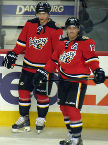 "Two hockey players in full uniform stand beside each other.  They are in matching red uniforms with black pants and black, white and yellow trim.  The jersey front says ""Calgary"" in script with a small stylized ""C"" logo."