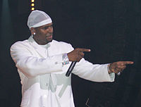 An African American man wearing white clothes and performing in a stage with a black background.