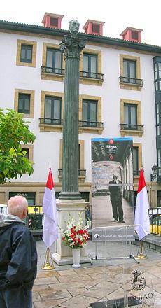 Banderas de Bilbao y flores rojas y blancas en el homenaje a Miguel de Unamuno, en la Plaza Unamuno, a unos cien metros de la casa natal del escritor, en el Casco Viejo de Bilbao
