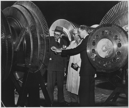 Belgian electrical engineers inspecting the rotor of a 40,000 kilowatt turbine of the General Electric Company in New York City Belgium. Belgian electrical engineers Georges Jean L. Van Antro, left, Georges H. Marchal, center, and Jacques de... - NARA - 541661.tif