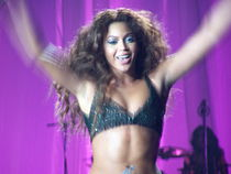 A brunette woman is smiling and holding her arms up. She wears a bra, and she perform on stage.