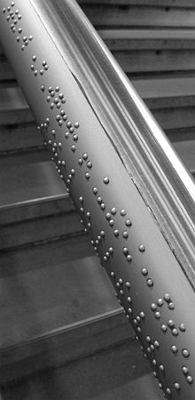 About 20 cm long section of a handrail made of gray steel, in the background you can see the stairs that lead up to it.  Along the side of the steel tube there are characters in Braille with small hemispheres.