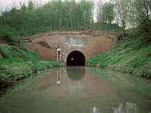 Red brick tunnel entrance to a tunnel through which light can just be seen at the far end. On either side are grassy banks down to the water.