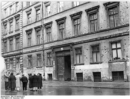 Members of a tenants' collective in front of their tenement building in East Berlin in 1959 (the facade still pockmarked with 1945 battle damage) Bundesarchiv Bild 183-69536-0010, Berlin, Marienstrasse, Wohnhaus, Altbau.jpg