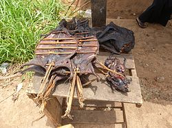 Several darkened animal carcasses with innards removed, some on thick wooden frames and skewers, stacked and resting on table near a person partly visible in the background.