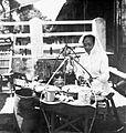 COLLECTIE TROPENMUSEUM Een vrouw bereidt voor de verkoop voedsel bij haar draagbare eetstal (warung) TMnr 10002651.jpg