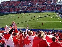 Photo d'un terrain pendant un match prise d'une tribune latérale. Au centre un fan porte le drapeau du Canada sur son dos.