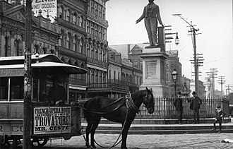 Bus advertising - A mule-drawn streetcar at Lafayette Square along St. Charles Avenue in New Orleans in the early 1890s. The front apron of the streetcar displays an advertisement for a performance of Trovatore! at the French Opera House.
