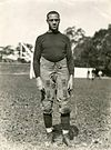 An African American male in an 1920s football uniform stands on a football field. Several unidentifiable individuals are in the visible in the distance
