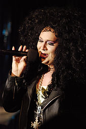 drag queen singing in to a microphone
