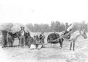 Stump Horn and family (Northern Cheyenne); showing home and horsedrawn travois.