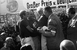 Peter Collins (racing driver) - Collins (left) and teammate Mike Hawthorn celebrate with race winner Juan Manuel Fangio, after the 1957 Groβer Preis von Deutschland