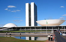The view shows a 20th-century building with two identical towers very close two each other rising from a low building which has a dome at one end, and an inverted dome, like a saucer, at the other.