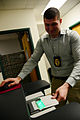 Derrek Taylor, an investigator with the U.S. Air Force's 733rd Security Forces Squadron, uncovers a live-scan machine at Joint Base Langley-Eustis in Virginia Dec. 18, 2013 131218-F-LG169-126.jpg