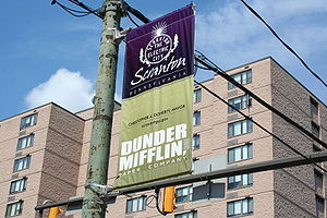 "The image is of street banner that reads ""Scranton"" and Dunder Mifflin""."