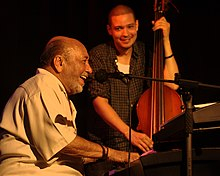 Eddie Palmieri performing in 2013 (left, with bassist Luques Curtis)