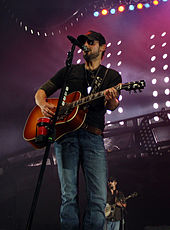 A man wearing a baseball cap, sunglasses and dark clothing, playing a guitar and singing into a microphone