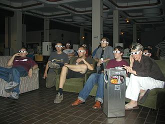 Demoscene - Evoke 2002: Spectators at one of the demoshow rooms watch computer animations in 3D.