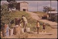 FATHER AND SONS FILL THEIR CONTAINERS AT THE COMMUNITY WATER PUMP. THIS IS A MOUNTAIN FARMING AREA - NARA - 546380.tif