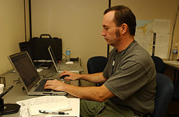 FEMA - 32323 - FEMA photographer Mark Wolfe working at a computer in Findlay, OH JFO