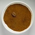 Finely grounded coffee beans in white bowl with intact roasted bean.png