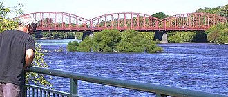 Baystate Marathon - A man on the waterfront of downtown Lowell, Massachusetts examines the Merrimack River near the final bridge of the Baystate Marathon course.