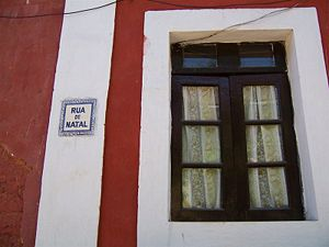 Fontainhas (quarter) - A typical house window in the bairro das fontainhas. Also seen in the picture is the street name displayed on an Azulejo (Portuguese ceramic tiling work).