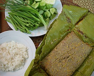 Cambodian cuisine - Prahok fried in banana leaves with fresh green vegetables and steamed rice.