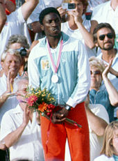 An African athlete wearing a light blue and white top and red shorts. He has a silver medal hanging from his neck and holds a posy of flowers.