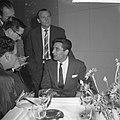 Gilbert Bécaud tijdens een persconferentie op Schiphol, Bestanddeelnr 911-6916.jpg