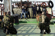 "On a boat, two soldiers are pointing guns at eight Arabic men. The soldiers are in green camouflage, they're kneeling and only their backs can be seen. One of them is wearing a ""camel water bag"" on his back. The Arabic sailors are wearing civilian clothing and all of them have their hands on their heads."