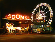 A red lighted sign with the word Dom and a lighted Ferris wheel in the background.