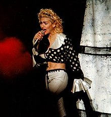 Madonna in a polka dotted blouse and white pants singing onstage