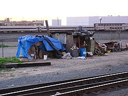 People experiencing homelessness living in cardboard boxes in Los Angeles, California where the median home price was estimated to be $564,430 in May 2006.
