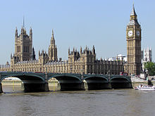 A colour photograph of the Palace of Westminster, containing the Houses of Parliament of the United Kingdom.  Photograph shows a long neo-gothic building with a clock tower at the right, with Westminster Bridge and the River Thames in the foreground.