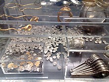 Transparent perspex box containing a shelf, two inner boxes, a large silver dish and many dozens of coins. The smaller inner box contains coins, whereas the larger contains two goblets and stacked ladles. The shelf holds gold bracelets, gold chains, and engraved spoons.