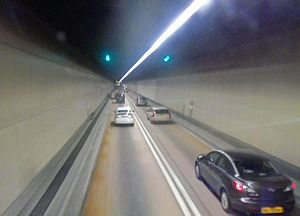 A two-lane road in a tunnel with plain brown sides and one overhead light strip.
