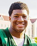 A picture of Jameis Winston while shaking someone's hand.