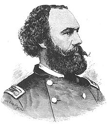 A black and white lithograph depicting a head and shoulders portrait of a United States Army officer of the Civil War era. He has curly black hair, a receding hairline and a large black mustache and beard. He is facing to the right and has a serious expression.