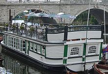 A barge moored near a large stone bridge, stern closest to the viewer, with a black hull and white cabin timbers with green trimmings. On the cabin roof, there are tables, chairs and parasols.